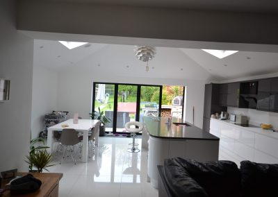 Internal view of completed of single storey kitchen and dining room extension showing multi fold doors and vaulted ceilin