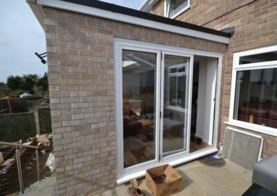 Rear view showing multi fold doors to the dining room of completed of single and two storey extensions creating lounge, dining room, kitchen and bedroom with en suite bathrooms