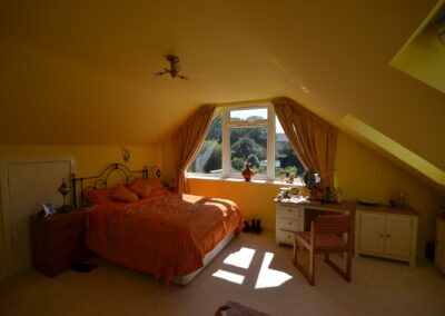 Internal view of first floor bedroom showing glazed gable end and roof windows of completed two storey lounge, utility room and bedroom extensions